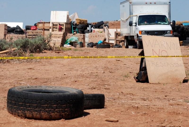 Police tape restricts access to a disheveled living compound in Amalia, N.M., on Tuesday, Aug. 7, 2018. (AP Photo)