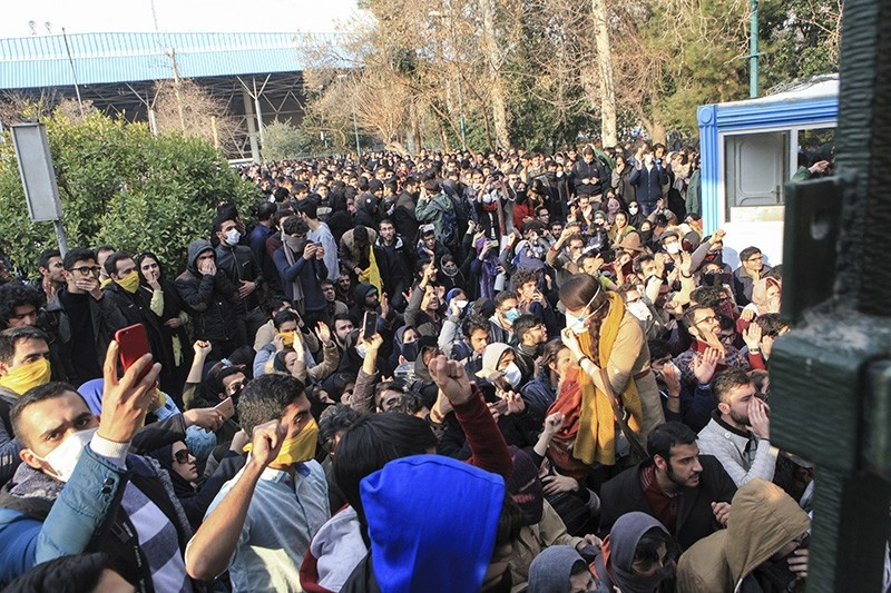 university students attend a protest inside Tehran University while anti-riot Iranian police prevent them to join other protestors, in Tehran, Iran (AP Photo)
