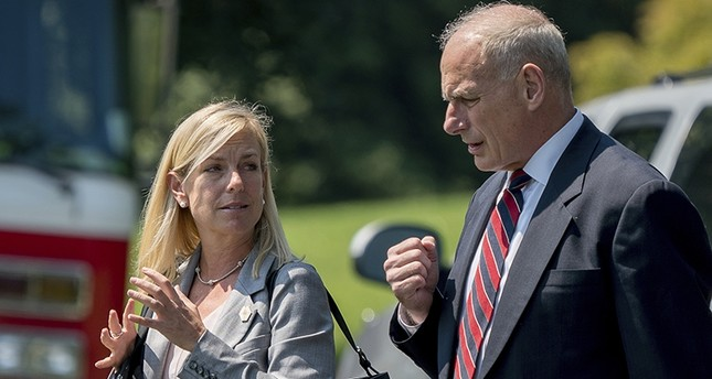 In this Aug. 22, 2017 photo, White House Chief of Staff John Kelly and Deputy Chief of Staff Kirstjen Nielsen speak together on the South Lawn of the White House in Washington. AP Photo