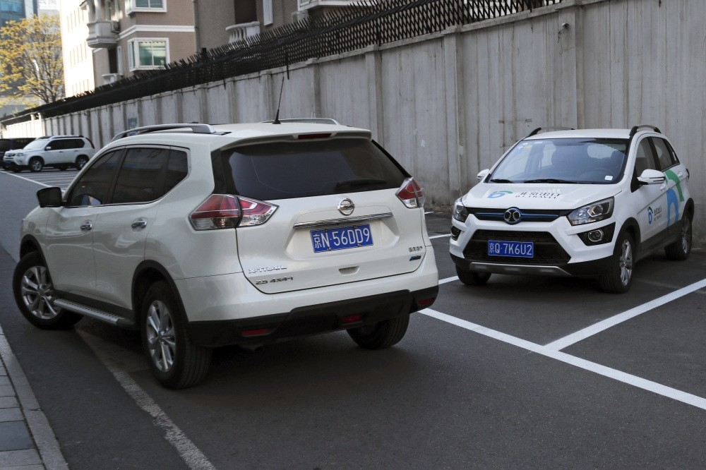 A SUV vehicle (L) drives past an electric-powered SUV parked outside a shopping mall in Beijing. This monthu2019s Shanghai auto show, industryu2019s biggest marketing event of year, will showcase efforts to create electric models Chinese drivers want to buy.
