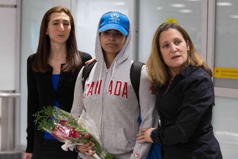Saudi teenager Rahaf Mohammed al-Qunun (C) is welcomed by Canadian Minister for Foreign Affairs Chrystia Freeland (R) as she arrives at Pearson International airport in Toronto, Ontario, on January 12, 2019 (AFP Photo)
