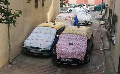 Residents prepare for the storm by covering their cars with blankets.