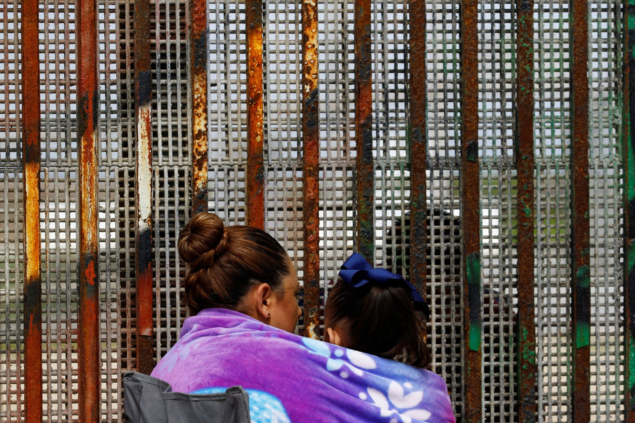 A woman carries her son while talking to her husband across the fence separating Mexico and U.S, as photographed from Tijuana, March 4, 2017. (REUTERS Photo)