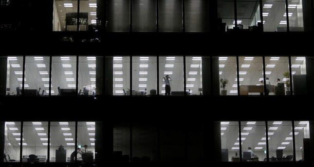 A man using his mobile phone stands near a glass window at a building in a Tokyo business district, Japan, March 18, 2015. (Reuters Photo)