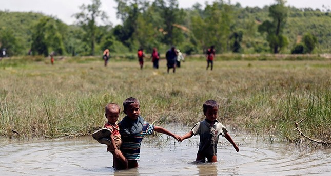Rohingya children make their way through water as they try to come to the Bangladesh side from No Man's Land after a gunshot being heard on the Myanmar side, in Cox's Bazar, Bangladesh August 28, 2017. (Reuters Photo)