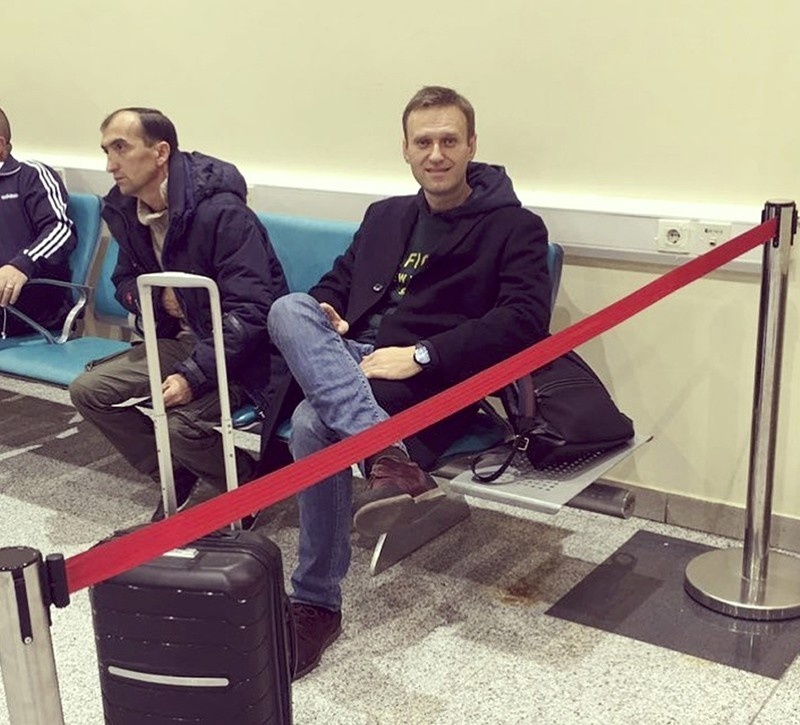 In this photo released by Anti-corruption Foundation Press Service, Russian anti-corruption activist Alexei Navalny sits behind a red ribbon at Domodedovo international airport outside Moscow, Russia, Tuesday, Nov. 13, 2018. (AP Photo)