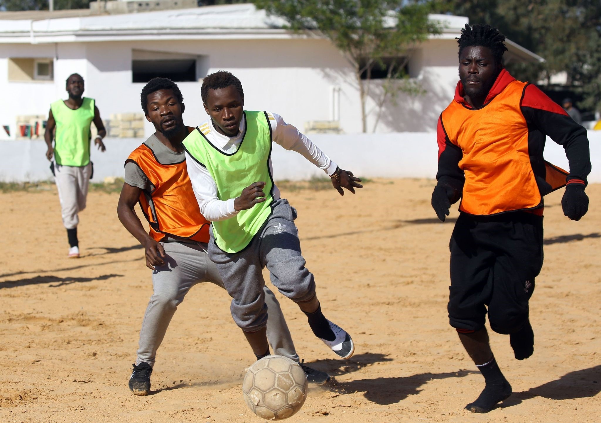 Cameroonian (orange) and Senegalese (yellow) African migrants, split into two teams for a football match at the Libyan Interior Ministryu2019s illegal migration shelter in Tajoura.