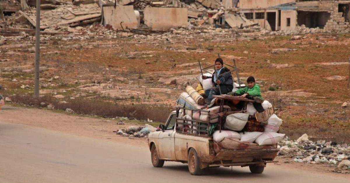 Displaced Syrians ride with their belongings as they flee bombardment in Aleppo, Jan.16, 2020. (AFP PHOTO)