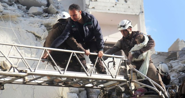 Syrian Civil Defence members evacuate a child from the rubble of a building destroyed following Russian airstrikes a day earlier on the northwestern city of Idlib on May 31.