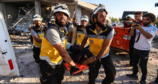 Members of White Helmets carry away a body on a stretcher following a reported government air strike in the village of Benin, about 30 kilometers south of Idlib in northwestern Syria, on June 19, 2019. (AFP Photo)