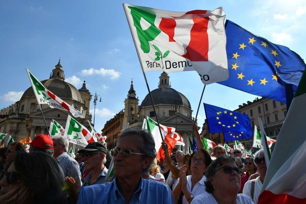 Supporters of Italy's center-left Democratic Party wave party flags and flags of the European Union as they gather for a rally in Piazza del Popolo in downtown Rome to protest the government policies, Sept. 30.