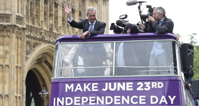 UKIP leader Nigel Farage waves to reporters during the launch of a new poster campaign ahead of the EU referendum in Smith Square, London Thursday.