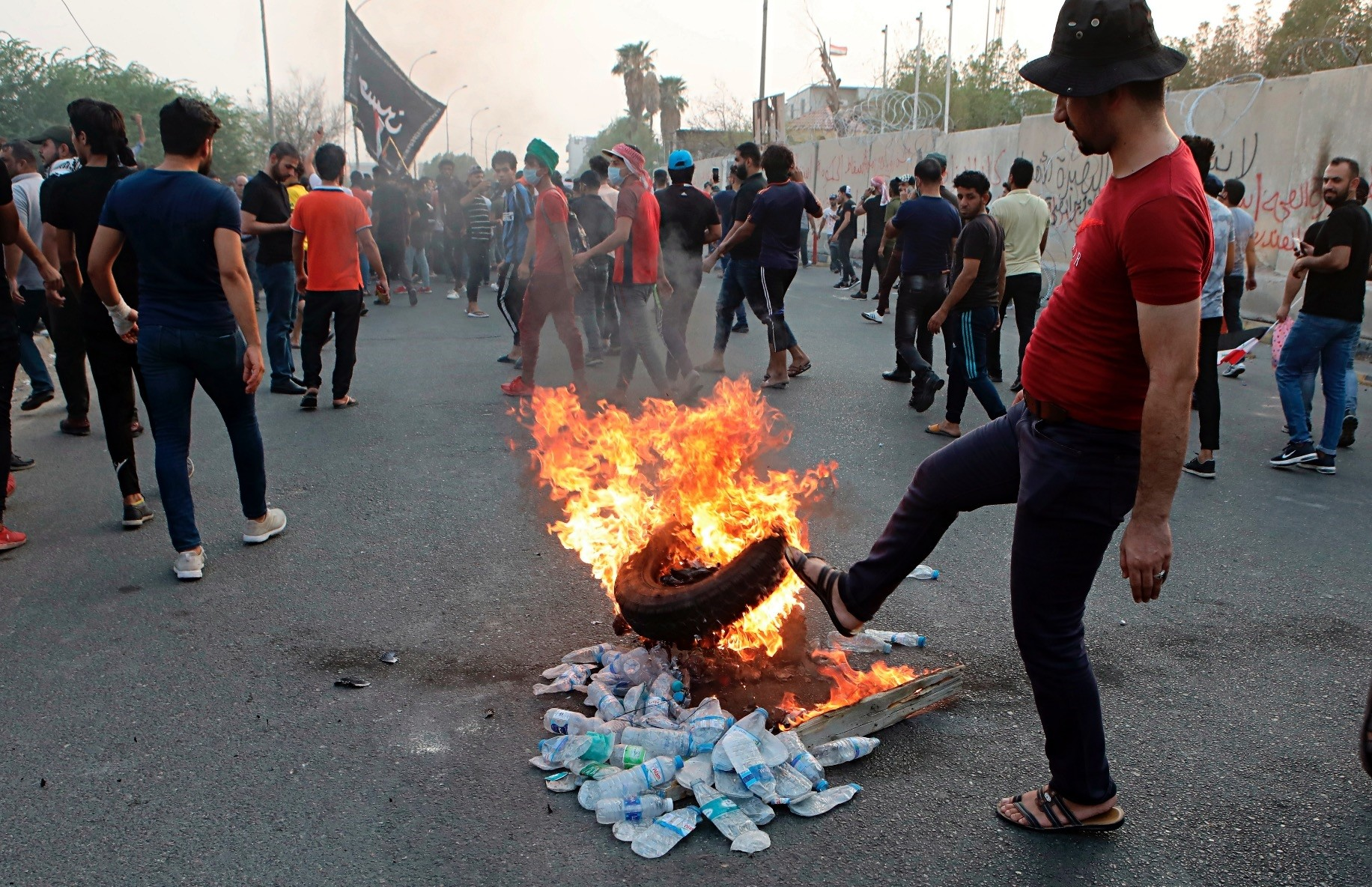Protesters set a tire on fire in front of the provincial council building, Basra, Sept. 4.