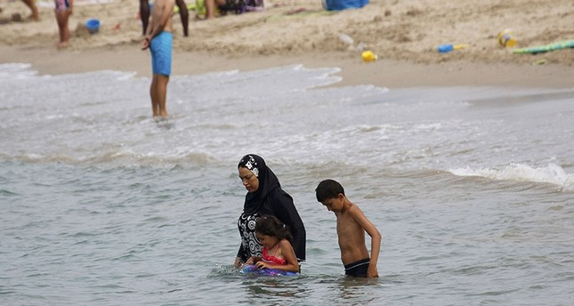 A Muslim woman wears a burkini, a swimsuit that leaves only the face, hands and feet exposed, on a beach in Marseille, France, August 17, 2016 (Reuters Photo)