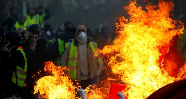 Protesters wearing yellow vests are seen behind a fire as they attend a demonstration of the yellow vests movement in Angers. (Reuters Photo)