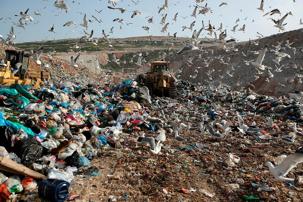 Earthmovers push mountains of garbage as seagulls fly over the country's largest landfill at Fyli on the outskirts of Athens. (AP Photo)