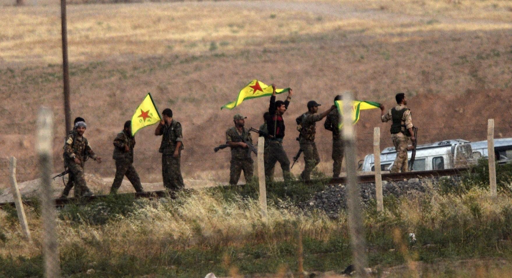 YPG terrorists hold flags near the Aku00e7akale border gate between Turkey and Syria, u015eanlu0131urfa, June 15, 2015.
