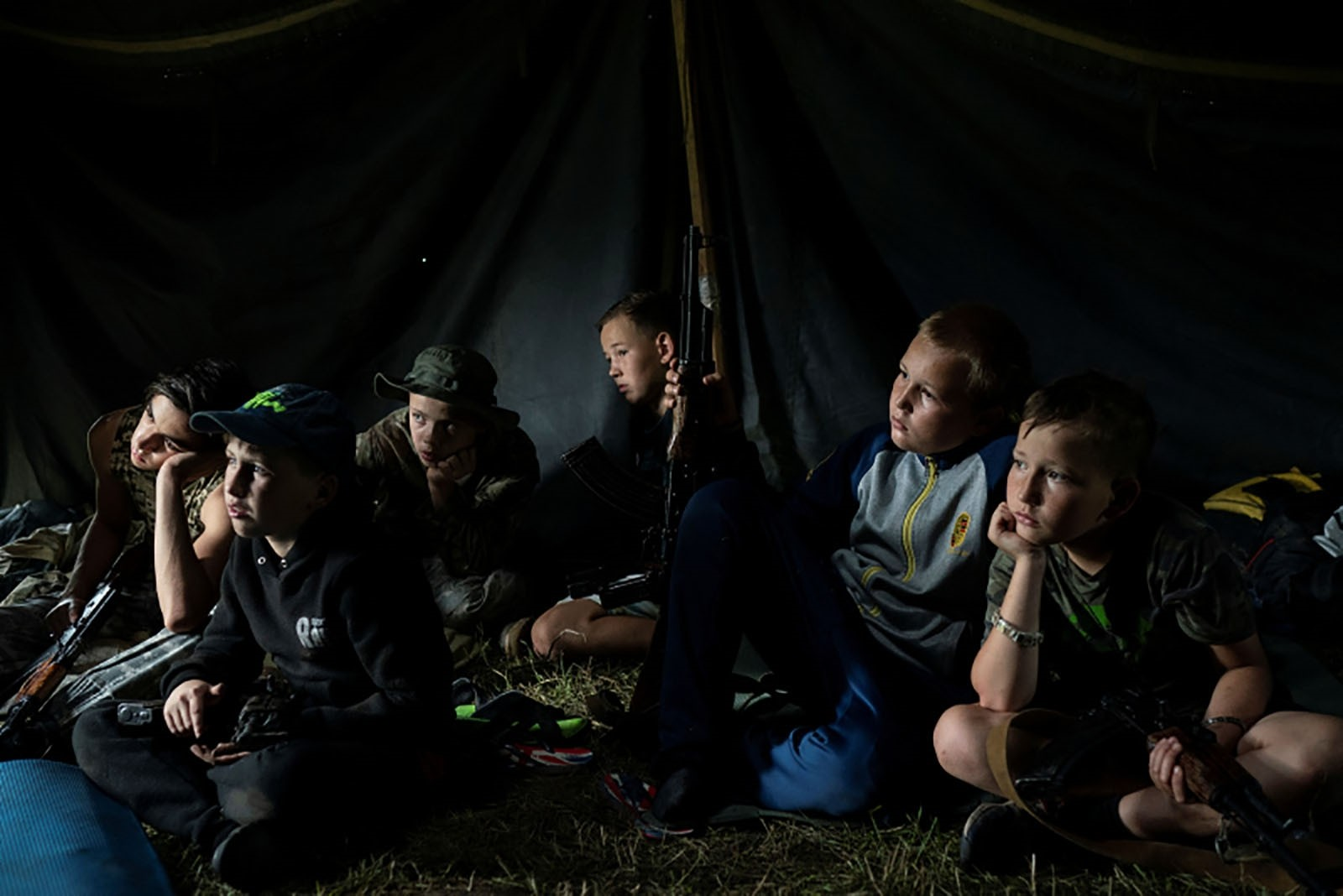 Young participants sit inside a tent with their AK-47 rifles as they receive instructions during a tactical exercise.