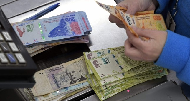 In this file photo taken on August 15, 2019 a cashier counts Argentine pesos bills at a supermarket in Buenos Aires. (AFP Photo)