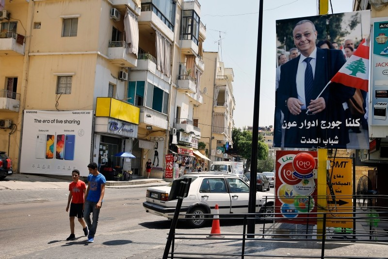 In this Monday, June 24, 2019 photo, a poster shows George Aoun, head of the municipality of the village of Hadat, with Arabic that reads ʺWe are all George Edward Aoun. |(AP Photo)