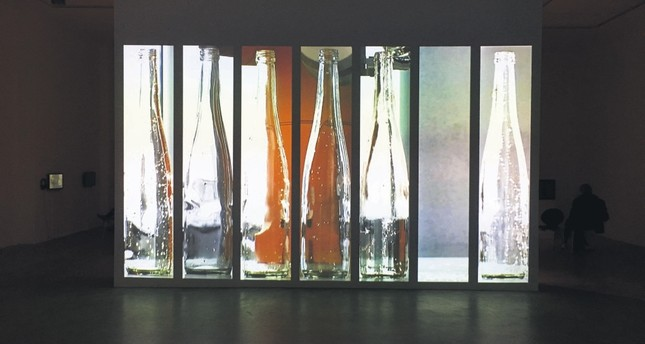 "The showcase starts with a huge, almost small cinema scale video projection of ""Re-Pouring"" (2010) that shows a robotic hand and six glass water bottles recorded vertically."