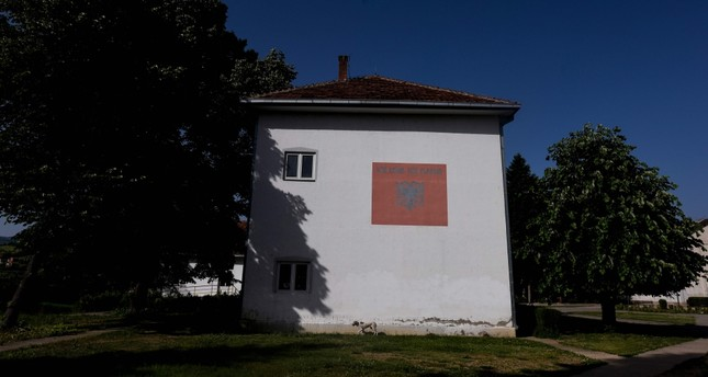 A school, featuring Albanian national flag painted on a side wall in the town of Kamenica on June 13, 2019.