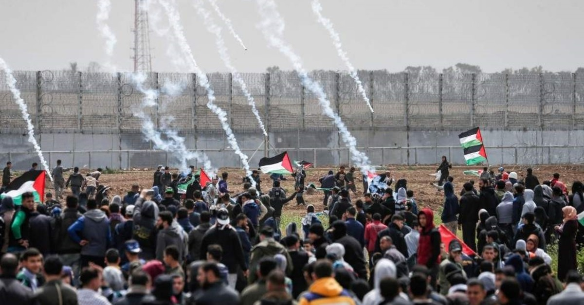 In this March 30, 2019, file photo, tear gas canisters fall among Palestinian protesters during a protest at the Gaza Strip's border with Israel. (AFP Photo)