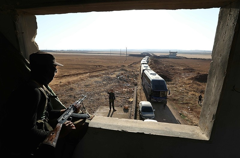 A member of Hayat Tahrir al-Sham group, led by Syria's former Al-Qaeda affiliate, watches as a convoy of buses gets ready to enter the towns of Fuaa and Kefraya to evacuate their residents on July 18, 2018. (AFP Photo)