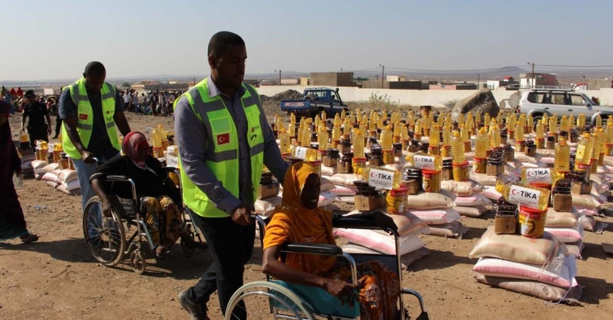 Tu0130KA workers help women in wheelchairs as they arrive to receive aid in Djibouti's Tadjourah region, June 12, 2019.