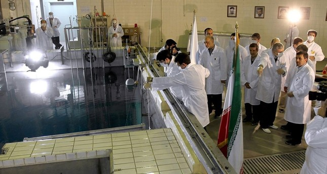 In this Feb. 15, 2012, file photo, provided by the Iranian President's Office, former Iranian President Mahmoud Ahmadinejad, right, is escorted by technicians during a tour of Tehran's research reactor center in northern Tehran, Iran. (AP Photo)