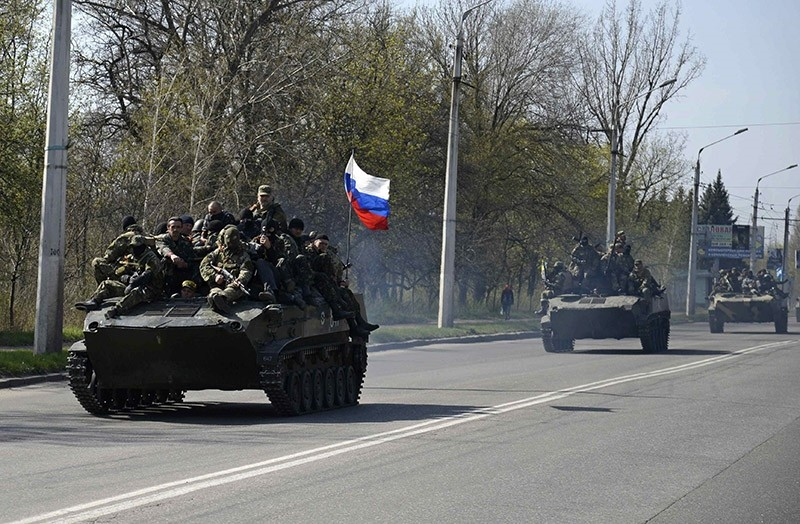Armed men, wearing black and orange ribbons of St. George - a symbol widely associated with pro-Russian protests in Ukraine, drive an airborne combat vehicle (L) with a Russian flag seen on the top, outside Kramatorsk April 16, 2014.  (Reuters Photo)