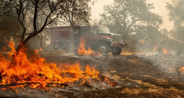 Firefighters douse a hotspot near various homes as the Carr fire continues to burn near Redding, California, on July 28, 2018. (AFP Photo)