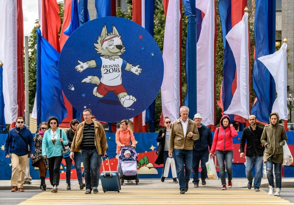 People walk in front of a 2018 FIFA World Cup decoration featuring the tournament mascot ,Zabivaka,, Moscow, June 7.