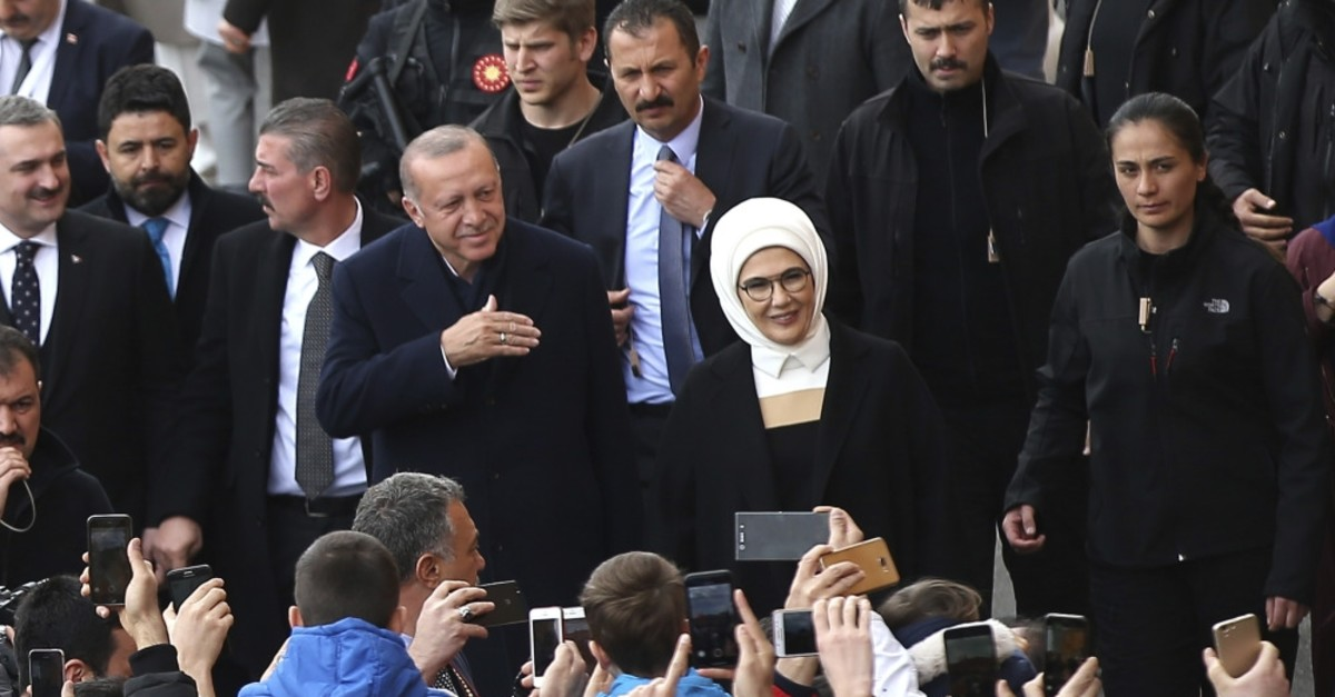 President Erdou011fan and his wife first lady Emine Erdou011fan wave to the people they arrive at a polling station in Istanbul, March 31, 2019.
