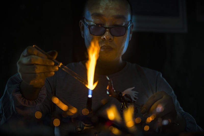 A technician works on shaping decorative glass pieces and jewelry in the traditional workshop in Zibo, Shandong Province, China, Sept. 9, 2018. (EPA Photo)