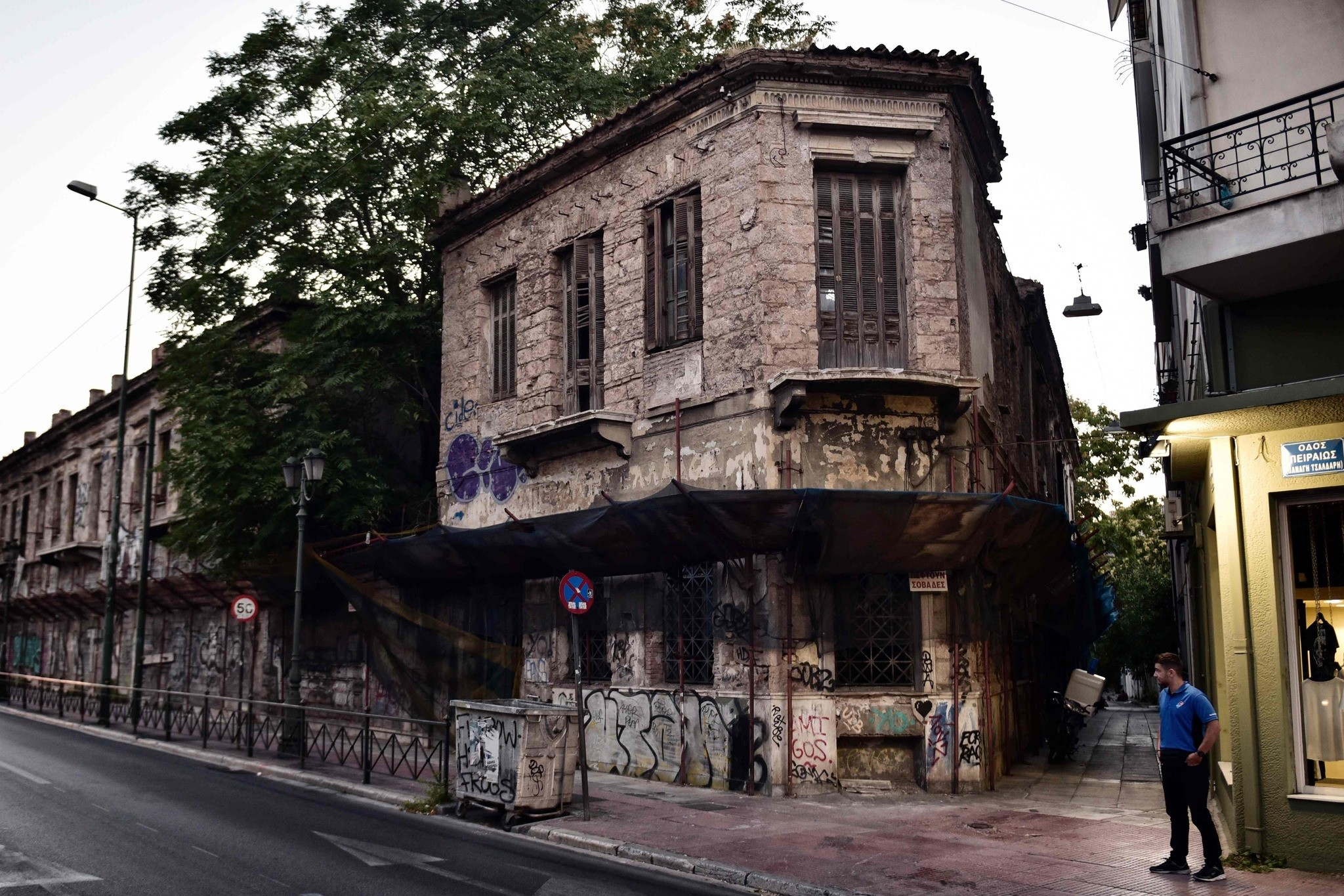 A man stands close to the abandoned neoclassical former Hatzikostas Orphanage in Athens.