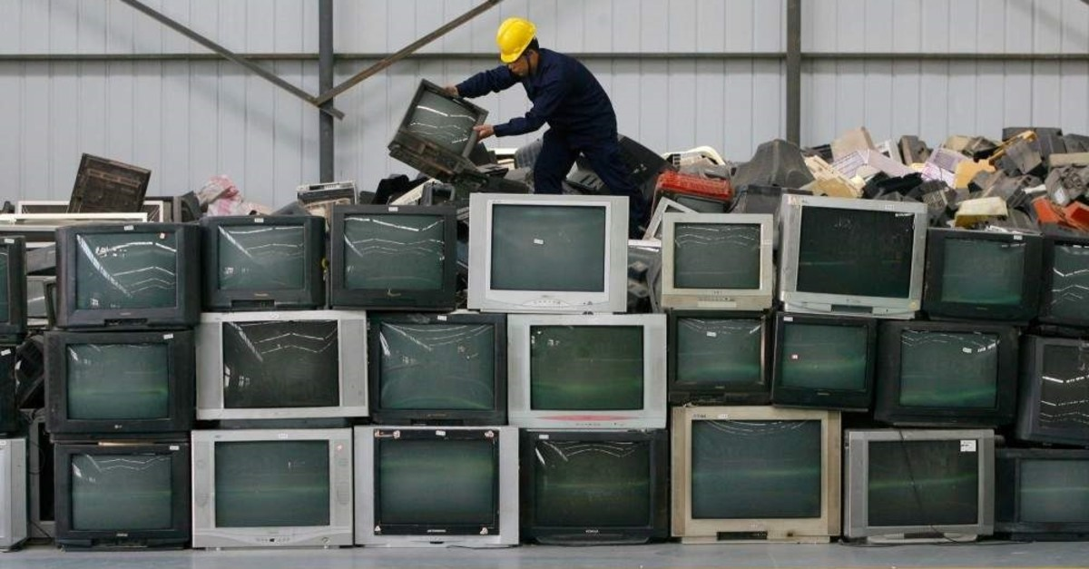 An employee arranges discarded televisions at a newly opened electronic waste recycling factory in China. (REUTERS)