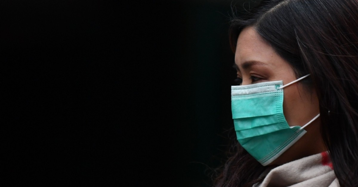 A pedestrian wears a surgical mask in London's China Town on January 24, 2020. (AFP Photo)