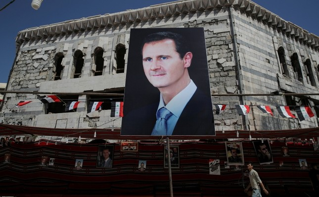 A man walks past a banner showing Bashar Assad in Douma, outside Damascus, Syria, Sept. 17, 2018. (Reuters Photo)
