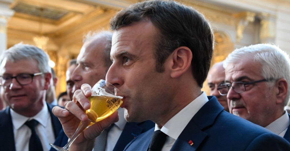French President Emmanuel Macron drinks a beer during a reception of the brewery sector in Paris on March 22, 2019. (AFP Photo)
