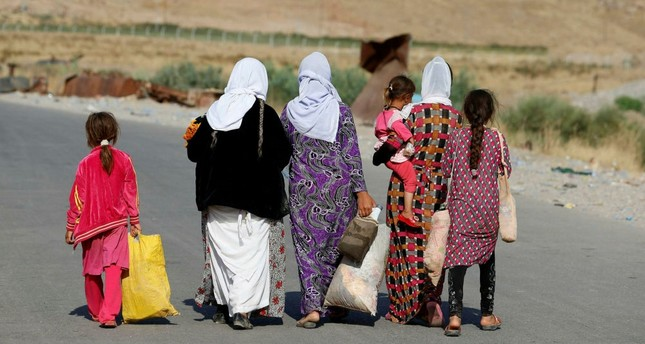 Women and children from the minority Yazidi sect, fleeing the violence in the Iraqi town of Sinjar, walk to a refugee camp.