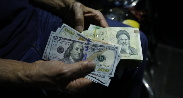 In this file photo taken on Aug. 8, 2018, a man exchanges Iranian Rials against U.S. dollars at an exchange shop in the Iranian capital Tehran. (AFP Photo)