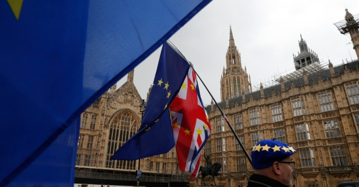 Anti Brexit demonstrators hold up their flags opposite the Houses of Parliament in London, Wednesday, April 3, 2019. (AP Photo)