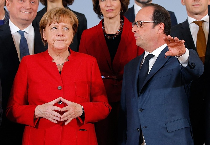 German Chancellor Angela Merkel (L) and French President Francois Hollande talk as they pose with ministers for a family picture during a joint Franco-German cabinet meeting in Metz, France, April 7, 2016. (Reuters Photo)