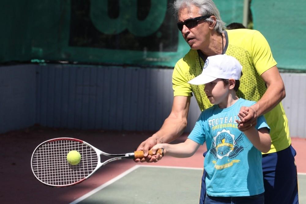 The Adana Tennis Federation's provincial representative Ferudun Au00e7an trains Syrian children.