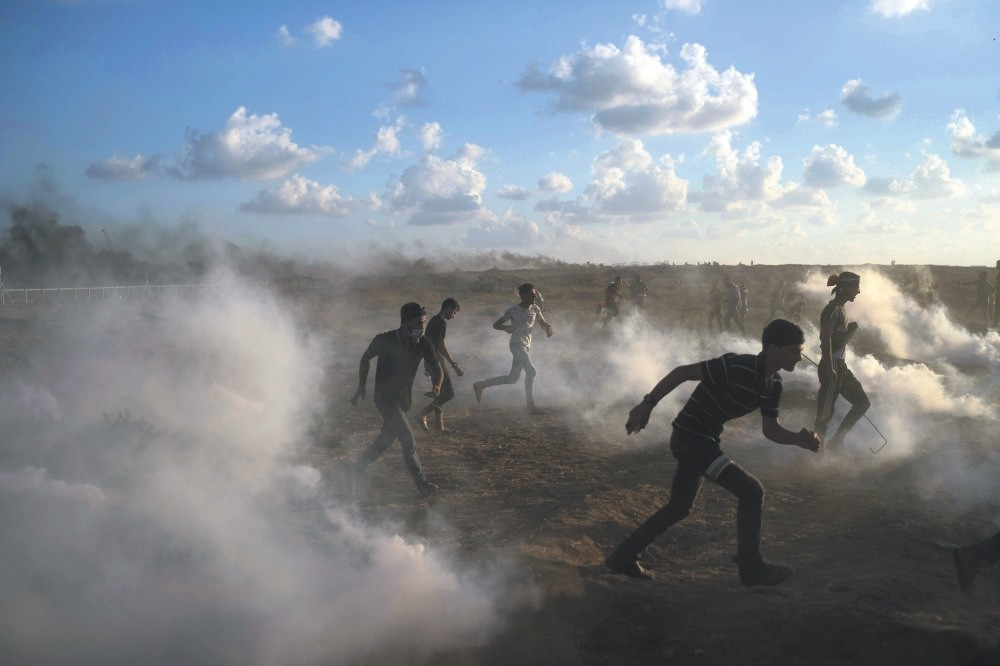 Palestinian protesters run from tear gas fired by Israeli troops during a protest at the Gaza Strip's border with Israel, Sept. 7, 2018.