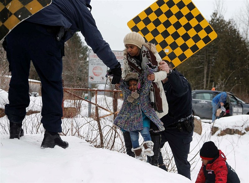 A woman from Sudan is taken into custody by Royal Canadian Mounted Police (RCMP) officers after arriving by taxi and walking across the U.S.-Canada border into Hemmingford (Reuters Photo)