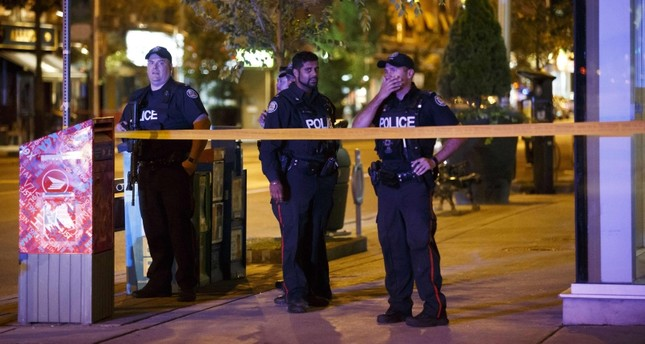 Toronto Police officers stand watch at Danforth St. at the scene of a shooting in Toronto, Ontario, Canada, July 23, 2018. (AFP Photo)