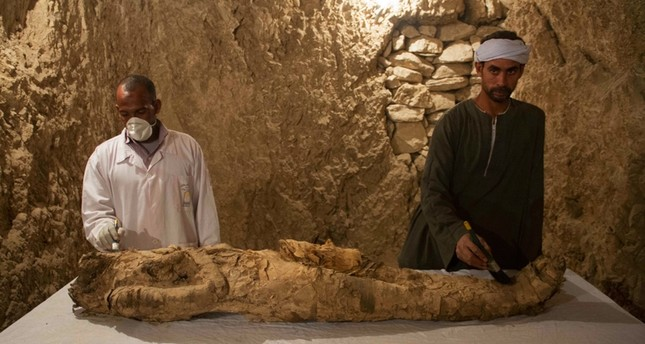Egyptian excavation workers restore a mummy in a newly discovered tomb in Egypt's Luxor ( AP Photo)