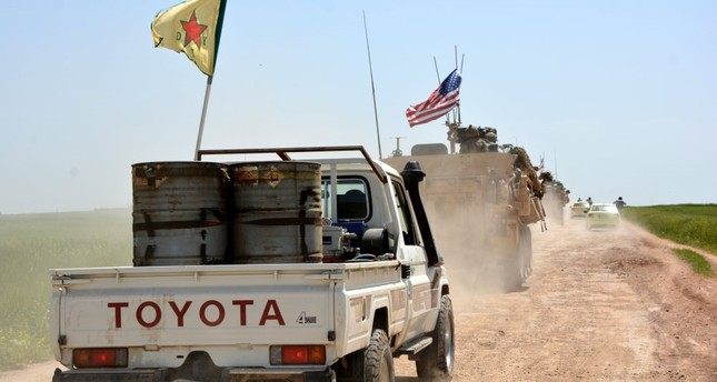 A convoy of U.S. army troops and militants from the PKK's Syrian affiliate the YPG patrol near al-Ghanamya, al-Darbasiyah along the Syrian-Turkish border, Syria, April 29.